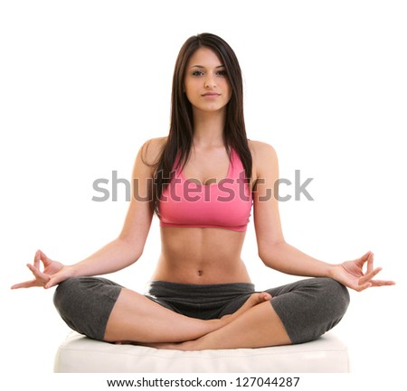 Portrait of fitness young woman sitting cross-legged in lotus position over white background. Horizontal shot. - stock photo