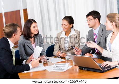 Portrait of five businesspeople sitting at the table and discussing important questions in the office - stock photo