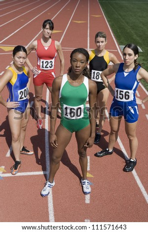 Portrait of five female athlete standing on track and field - stock photo
