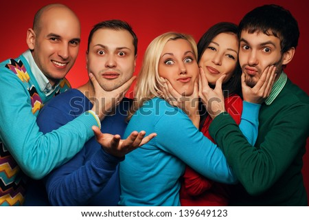 Portrait of five stylish close friends hugging, smiling and posing over red background. Guys having fun and holding cheeks of their neighbor. Hipster style. Studio shot - stock photo