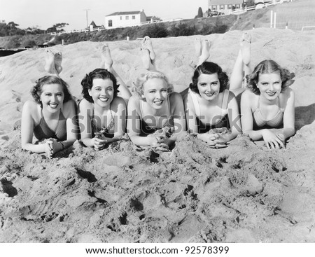 Portrait of five young women lying on the beach and smiling - stock photo