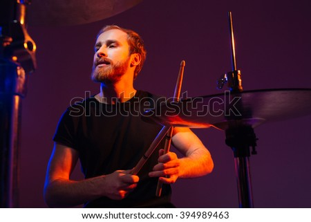 Portrait of focused handsme bearded drummer playing drums over dark background - stock photo