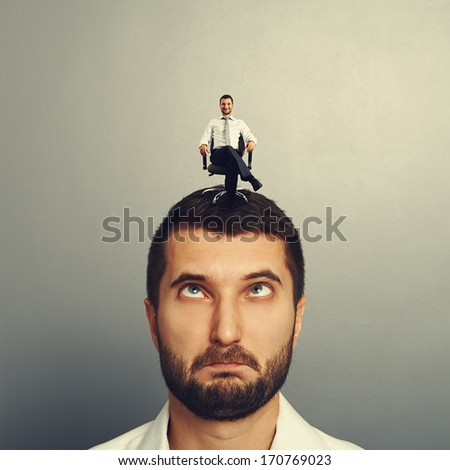portrait of foolish man with small smiley man on the head - stock photo