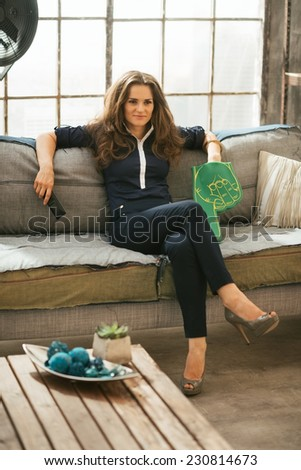 Portrait of football fan woman watching tv in loft apartment - stock photo