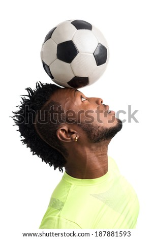Portrait of footballer balancing a ball on his head - stock photo