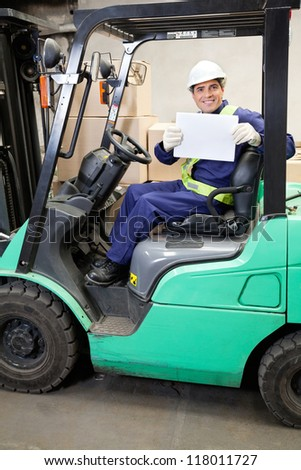 Portrait of forklift driver displaying blank placard - stock photo