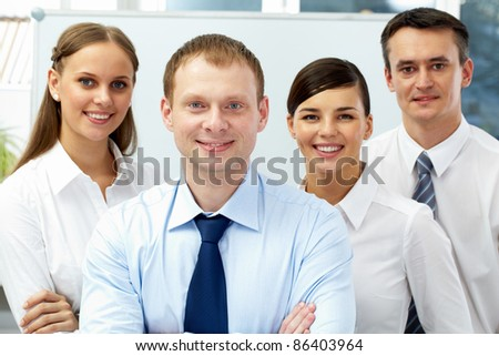 Portrait of four businesspeople, looking at camera and smiling - stock photo