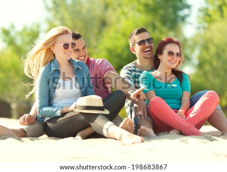 Portrait of four cheerful young friends enjoying outdoors - stock photo