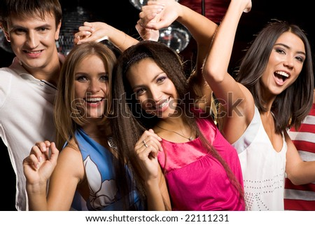 Portrait of four clubbing friends looking at camera with smiles while dancing - stock photo
