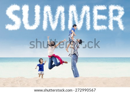 Portrait of four family members having fun on the tropical beach under a summer's cloud - stock photo