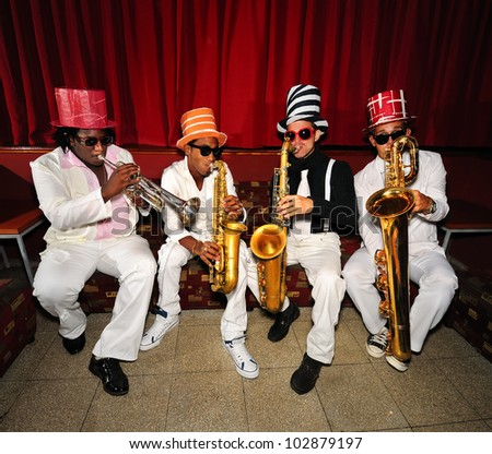 Portrait of four funky musicians playind wind instruments, saxo, trumpet. - stock photo