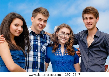 Portrait of four happy smiling group of young people teenage friends boys and girls outdoors against blue sky background - stock photo