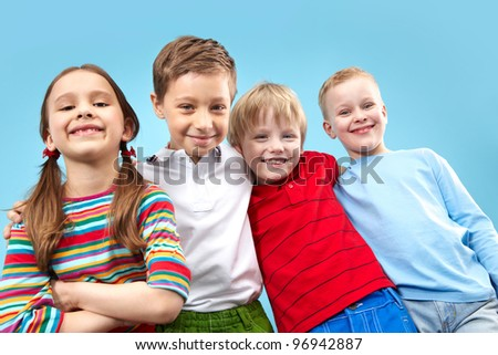 Portrait of four kids looking at camera with a confident smile - stock photo
