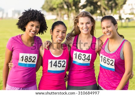 Portrait of four smiling runners supporting breast cancer marathon in parkland - stock photo