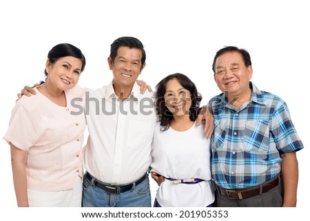 Portrait of four smiling senior people hugging and looking at the camera - stock photo