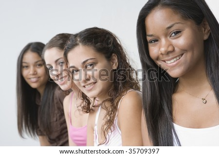 Portrait of four teenage girls smiling against white background. - stock photo