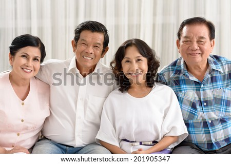 Portrait of four Vietnamese retired people sitting on the sofa and looking at the camera - stock photo