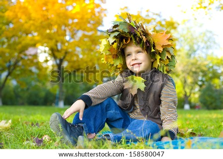 Portrait of four-year-old boy who sits on grass in a wreath from autumn leaves - stock photo