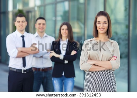 Portrait of four young and successful business people. Focus on confident young businesswoman standing with her arms crossed in front of her business team. - stock photo