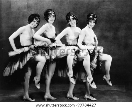 Portrait of four young women performing a dance - stock photo