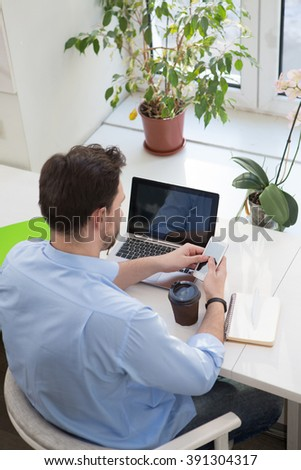 Portrait of freelance man using mobile phone while sittin in restaurant. cafe or office with laptop computer. Handsome man drinking coffee. - stock photo