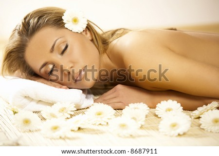 Portrait of Fresh and Beautiful blond woman laying on bamboo mat around flowers and taking spa treatment - stock photo
