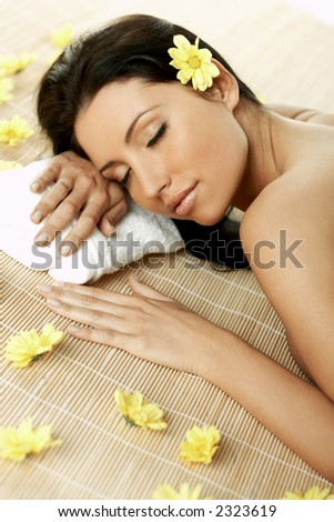 Portrait of Fresh and Beautiful brunette woman laying on bamboo mat around yellow flowers - stock photo