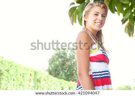 Portrait of fresh healthy beauty portrait of a young blond teenager caucasian woman turning and looking at camera, smiling on a sunny summer day, home exterior. Adolescent girl, outdoors lifestyle. - stock photo