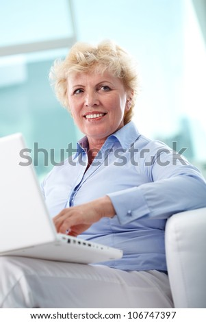 Portrait of friendly aged woman typing and smiling - stock photo