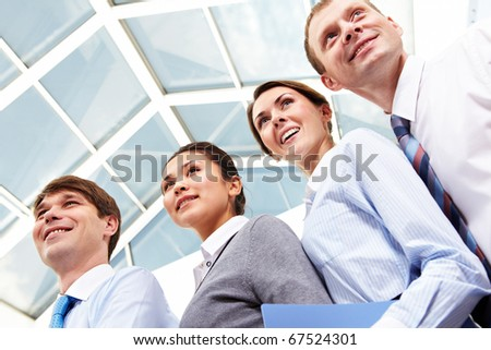 Portrait of friendly business people standing next to each other and smiling - stock photo