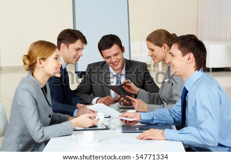 Portrait of friendly colleagues looking at each other while confident woman sharing her idea with co-workers on background - stock photo