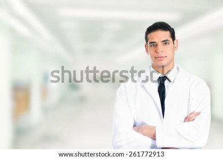 Portrait of friendly confident male doctor smiling arms folded standing in hospital clinic hallway corridor  - stock photo
