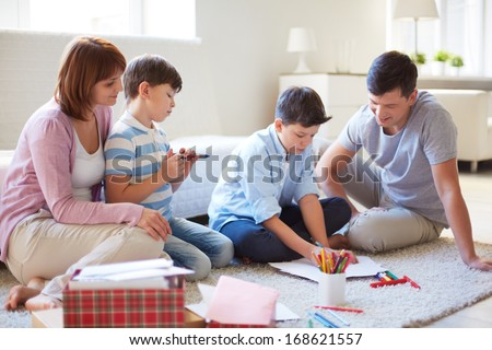 Portrait of friendly family drawing together at home - stock photo