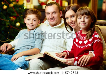 Portrait of friendly family with book looking at camera on Christmas evening - stock photo