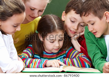 Portrait of friendly group reading book in classroom - stock photo