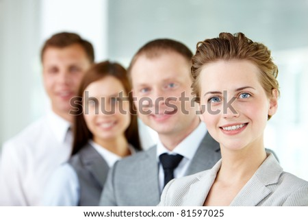 Portrait of friendly leader looking at camera with three employees behind - stock photo