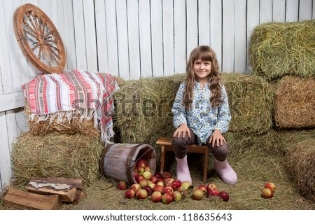 Portrait of friendly little blond girl villager sitting on stool near inverted pail with apples in wooden hayloft during harvest time - stock photo