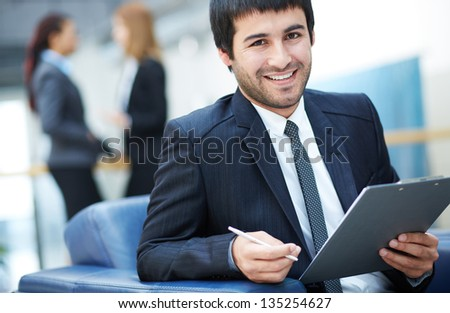 Portrait of friendly male leader looking at camera in working environment - stock photo