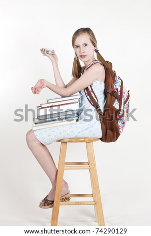 Portrait of friendly school girl student with backpack, sitting on a stool, holding notebooks and talking on a mobile phone - stock photo