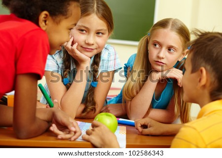 Portrait of friendly schoolchildren chatting in classroom - stock photo