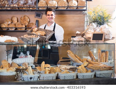 Portrait of friendly smiling man at bakery display with pastry - stock photo