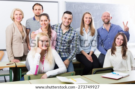 Portrait of friendly teacher and adult students in classroom - stock photo