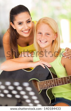 portrait of friendly teacher with her music learner - stock photo