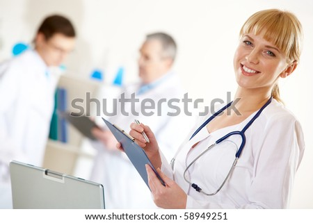 Portrait of friendly therapist looking at camera in working environment - stock photo