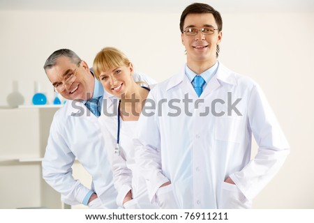 Portrait of friendly therapists standing in line and looking at camera with happy clinician in front - stock photo