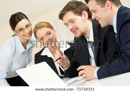 Portrait of friendly workteam looking at monitor of laptop while confident businessman pointing at screen - stock photo