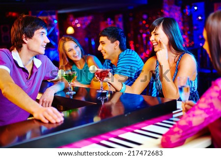 Portrait of friendly young people having cocktails in the bar - stock photo