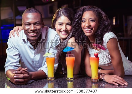 Portrait of friends enjoying while having cocktail drinks at bar counter in bar - stock photo