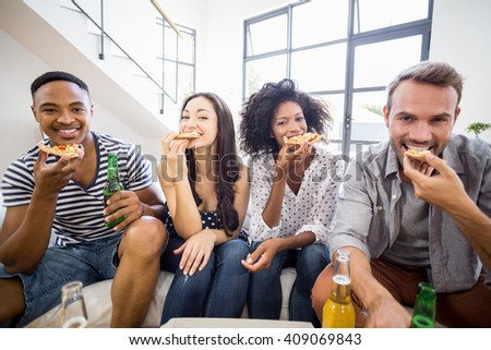 Portrait of friends having a pizza in living room - stock photo