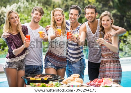 Portrait of friends having juice at outdoors barbecue party near pool - stock photo